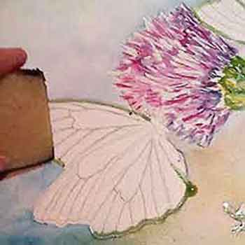 Remove the masking from the butterfly wings before painting them.